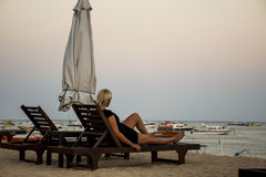 Bali Indonesia girl sitting at Sanur Beach sunset Royalty Free Stock Photo