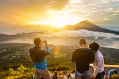 Group of young people watch the dawn. BALI, INDONESIA - JANUARY 7, 2018: Group of young people watch the dawn on top of the Batur volcano in Bali, Indonesia Stock Images