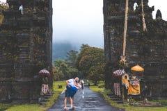 BALI, INDONESIA - JANUARY 3, 2019: Young honeymoon couple on a big balinese gates background. Bali island, Indonesia. royalty free stock photo