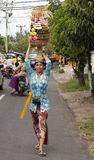 BALI, INDONESIA - JUL 8TH: A woman carries a basket of fruit to Stock Photos