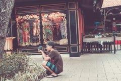 BALI, INDONESIA - JUNE 30, 2017: Asian street photographer making shots, Bali island. Royalty Free Stock Photography
