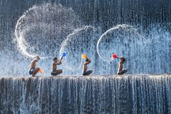 Children playing splash the water at Klungkung Dam. Bali, Indonesia - June 10,2017: Children enjoy playing splash the water at Klungkung Dam or Dam Tukad Yeh royalty free stock photography