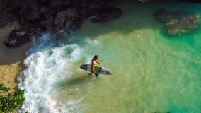 Bali, Indonesia - 25 June 2016: Unidentified surfer entering sea. BALI, INDONESIA - 25 JUNE 2016 Unidentified surfer entering sea at Blue Uluwatu point Stock Images