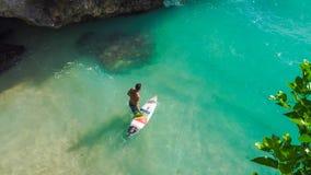 Bali, Indonesia - 25 June 2016: Unidentified surfer entering sea. BALI, INDONESIA - 25 JUNE 2016 Unidentified surfer entering sea at Blue Uluwatu point Royalty Free Stock Image