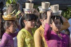 BALI, INDONESIA 6 LUGLIO: Le ragazze di balinese portano le offerti alla t Immagini Stock