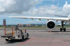 BALI/INDONESIA-, 27. MÄRZ 2019: Maschine und Hauptfahrwerk wenn Flugzeugpark auf Schutzblech im Flughafen mit irgendeinem Fahrzeu lizenzfreies stockfoto