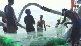 Bali, Indonesia - maggio 2019: pescatore sulla riva di mare che ottiene pesce di cattura dalla rete da pesca Pescatori che selezi video d archivio
