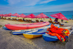 BALI, INDONESIA - MARCH 11, 2017: Beautiful sunny day with a row of red unmbrellas and some boats on the yellow sand, in Royalty Free Stock Photo