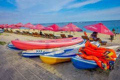 BALI, INDONESIA - MARCH 11, 2017: Beautiful sunny day with a row of red unmbrellas and some boats on the yellow sand, in Stock Photography