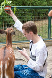 BALI, INDONESIA - March 22, 2017: Tourist man feeding young deers from hands and making shoots on his smartphone in Bali Royalty Free Stock Photo
