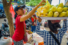 BALI, INDONESIA - MARCH 08, 2017: Unidentified woman buying food, while other woman is balancing over her head food, in Stock Images