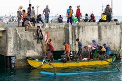 BALI/INDONESIA-MAY 15 2019年:一些巴厘语传统小船乘客到达船坞和步行对大陆 他们使用黄色 图库摄影