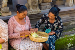 Bali, Indonesia, May 3, 2015. Balinese women make decorations of Royalty Free Stock Photo