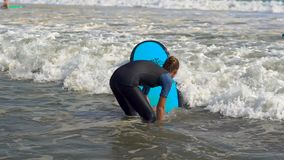 Bali, Indonesia - May. 12 : Slowmotion shot of a young woman on a surfing training lesson struggling with waves stock footage