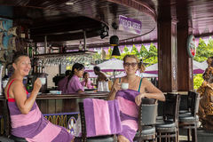 BALI, INDONESIA - MAY 5, 2017: Two women drinking coffe and relaxing in swimming pool bar and restaraunt. Bali. Stock Photo