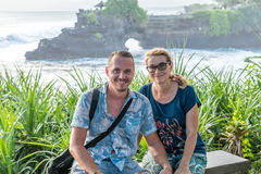 BALI, INDONESIA - MAY 4, 2017: Woman and her son on a background of Pura Tanah lot temple, Bali island, Indonesia. Stock Photo