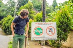 BALI, INDONESIA - 21 May, 2018: Young man looks at protest sign on a wall in Indonesian objecting to Uber and Grab taxi royalty free stock photos