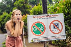 BALI, INDONESIA - 21 May, 2018: Young woman looks at protest sign on a wall in Indonesian objecting to Uber and Grab stock image