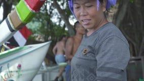 Bali, Indonesia - mayo de 2019: esposa del pescador que prepara la red de pesca en orilla de mar en fondo del barco de los pescad almacen de video