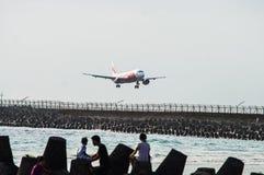 Bali, Indonesia - November 25, 2012: AirAsia Airbus A320 landing. At Ngurah Rai International Airport on runway protruding in sea Stock Photos