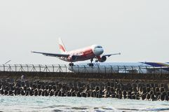 Bali, Indonesia - November 25, 2012: AirAsia Airbus A320 landing. At Ngurah Rai International Airport on runway protruding in sea. Airbus A340 Thai Airways in Stock Photos
