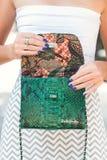 BALI, INDONESIA - NOVEMBER 15, 2017: Closeup of luxury snakeskin python handbag in woman hands. Brand BaliSnake Stock Photo
