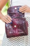 BALI, INDONESIA - NOVEMBER 15, 2017: Closeup of luxury snakeskin python handbag in woman hands. Brand BaliSnake Royalty Free Stock Photo