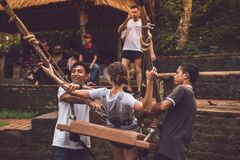 BALI, INDONESIA - NOVEMBER 25, 2017: Two men helping a girl to sit down on a swings on the cliff. Tropical Bali island.  Royalty Free Stock Photos