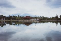 Bali, Indonesia: Panoramic view of building on lake shore with reflection in water stock photo
