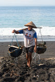 Traditional sea salt production on the volcanic black sand, Bali. BALI, INDONESIA - SEP 26: Worker collects water for sea salt production on Sep 26, 2012 in Amuk Royalty Free Stock Photography