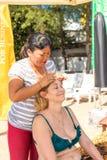 BALI INDONESIEN - APRIL 14, 2017: Den höga kvinnan får den head massagen på stranden arkivfoton