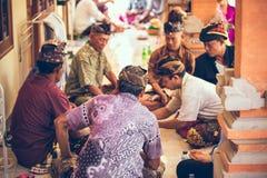 BALI INDONESIEN - APRIL 13, 2018: Grupp av balinesemän som spelar kort som sitter på golvet Bali ö Royaltyfri Bild