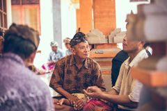 BALI INDONESIEN - APRIL 13, 2018: Grupp av balinesemän som spelar kort som sitter på golvet Bali ö Arkivfoton