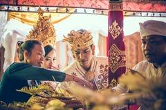 BALI INDONESIEN - APRIL 13, 2018: Nygifta personer på balinesebröllopceremoni Traditionellt bröllop Fotografering för Bildbyråer