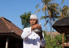 BALI INDONESIEN - AUGUSTI 29,2012: En präst som rymmer en skyttel med arkivfoton