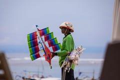BALI INDONESIEN - 16 11 2017: Balinesemannen säljer handgjorda drakar på den Bali stranden, Indonesien Arkivfoto