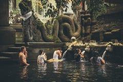 BALI INDONESIEN - DECEMBER 5, 2017: Heligt vårvatten Folk som ber i den Tirta Empul templet bali indonesia royaltyfri fotografi
