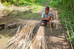 BALI, INDONESIEN - 25. DEZEMBER 2016: Balinesemann, der Bambus schnitzt Stockfotografie