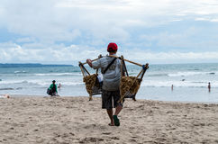 BALI, INDONESIEN IM JANUAR 2017: Erdnussverkäufer geht entlang Kuta-Strand und versucht, lokale Erdnüsse an Touristen zu verkaufe Stockbilder