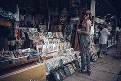 BALI INDONESIEN - JANUARI 1, 2017: Ung kvinna på souvenirgatan av Ubud, Bali, Indonesien royaltyfria bilder