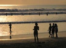 BALI - INDONESIEN - JULI 2007: Folket tycker om en bedöva solnedgång på den Kuta stranden arkivbild