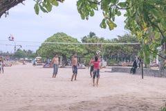 BALI INDONESIEN - JULI 27, 2017: Grupp av vänner som spelar strandsalvan - Mång--etik grupp människor som har gyckel på royaltyfri fotografi