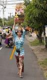 BALI INDONESIEN - JULI 8TH: En kvinna bär en korg av frukt till Arkivfoton
