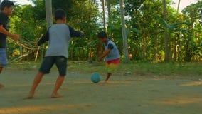 Bali/Indonesien - Juni 2019: Indonesiska barn älskar fotboll En grupp av ungar som spelar fotboll som är barfota på solnedgång br arkivfilmer