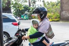 BALI INDONESIEN - JUNI 2, 2017: Stående av balinesemodern med hennes barn i händer som sitter på mopeden royaltyfria bilder