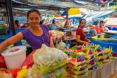BALI, INDONESIEN - 8. MÄRZ 2017: Nicht identifizierte Frau tun eine Anordnung für Blumen innerhalb eines Kastens, der von den Blä Lizenzfreies Stockbild