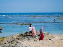 BALI, INDONESIEN - 11. MÄRZ 2017: Nicht identifizierte Leute, die den schönen sonnigen Tag und den weißen Sand im Strand genießen Stockbild