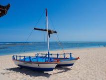 BALI, INDONESIEN - 11. MÄRZ 2017: Schöner sonniger Tag mit einem Boot auf dem mit gelbem Sand im Strand von Pantai-pandawa, herei Lizenzfreies Stockfoto