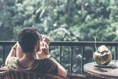 BALI, INDONESIEN - 17. MAI 2018: Mann mit der frischen organischen Kokosnuss, die auf einem watefall Hintergrund im Dschungel von Lizenzfreie Stockfotografie