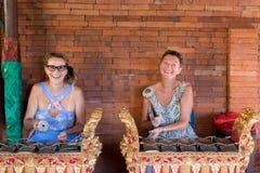 BALI INDONESIEN - MAJ 5, 2017: Kvinnor som spelar på traditionella det gamelan Balinesemusikinstrumentet man för bali town för so royaltyfria foton